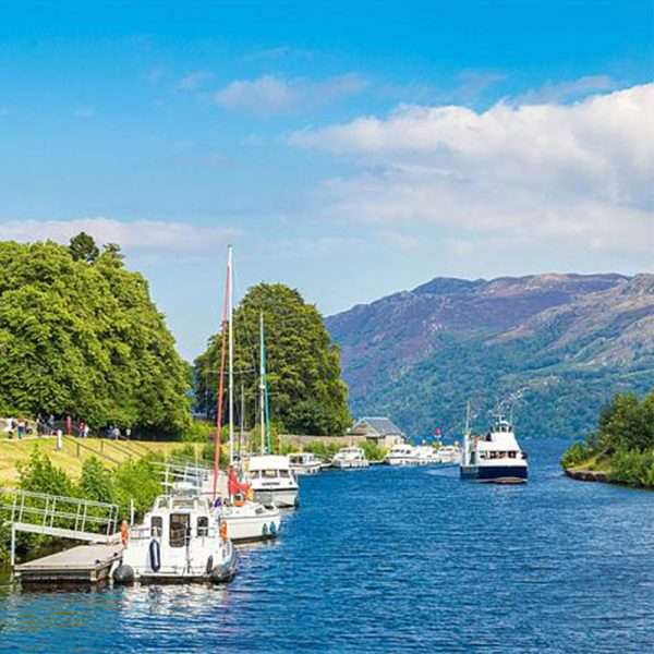 The Caledonian Canal with boats on it and people walking along it and Loch Ness up ahead